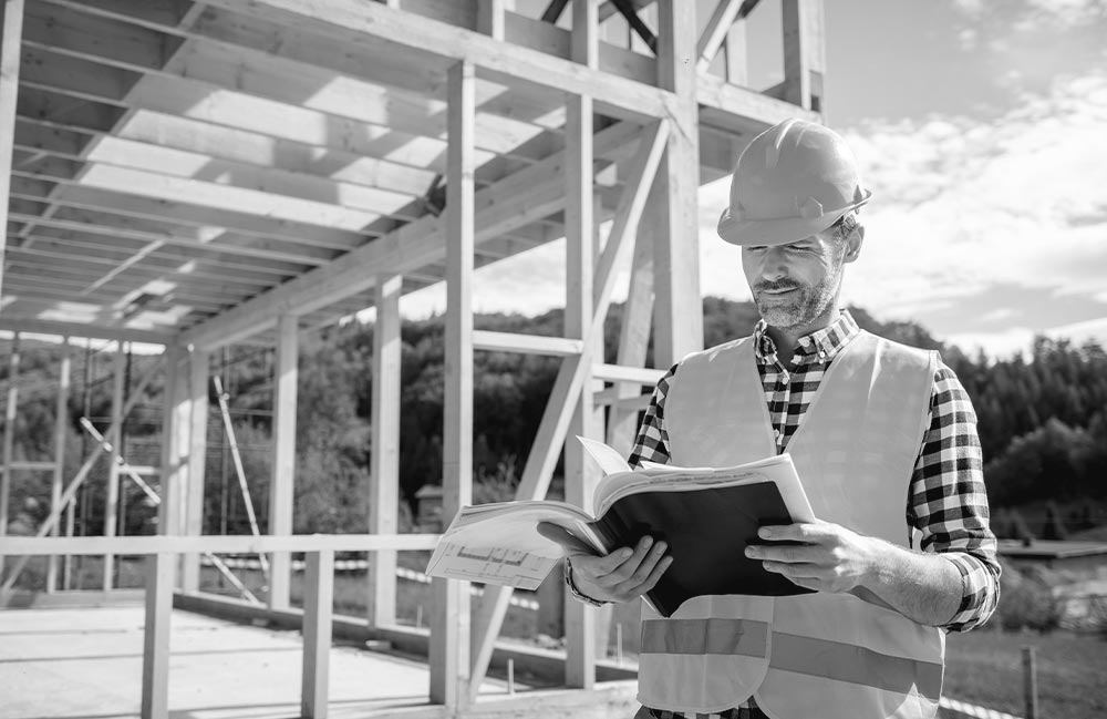 engineer-with-hardhat-and-blueprints-on-building